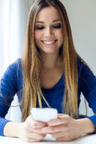 Young beautiful woman using her mobile phone at home. Royalty Free Stock Image