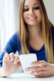 Young beautiful woman using her mobile phone at home. Royalty Free Stock Photo