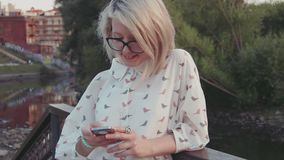 Young beautiful woman using her smartphone in the city park near the lake texting her friends browsing internet stock video