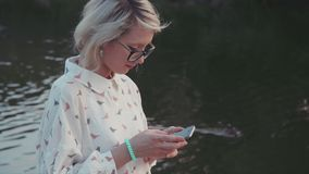 Young beautiful woman using her smartphone in the city park near the lake texting her friends browsing internet. Stock footage of a young beautiful woman using stock video footage
