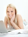 Young beautiful woman using laptop in bed Stock Image