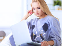 Young beautiful woman using a laptop computer at home Stock Photography