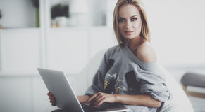 Young beautiful woman using a laptop computer at home Stock Images
