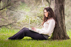 Young beautiful woman using a laptop computer at the park Royalty Free Stock Image