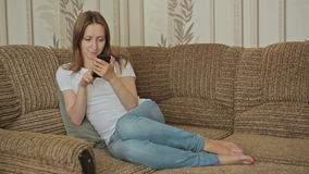 Young beautiful woman using smartphone in home stock video