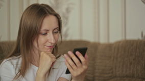 Young beautiful woman using smartphone in home. Young woman and digital technology, pretty caucasian girl chatting and text messaging on mobile phone sitting on stock video footage