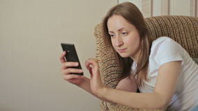 Young beautiful woman using smartphone in home. While sitting on sofa stock footage
