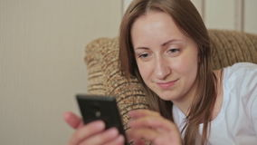 Young beautiful woman using smartphone in home. While sitting on sofa stock video