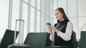 Young beautiful woman is using a smartphone while waiting for a train as arrival. attractive young blonde woman using. Smart-phone while standing on the railway stock footage