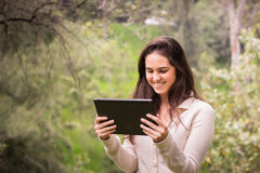 Young beautiful woman using a tablet computer at the park Royalty Free Stock Photo