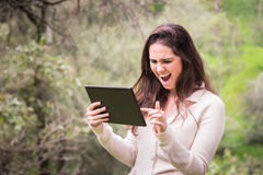 Young beautiful woman using a tablet computer at the park Royalty Free Stock Photography