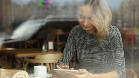 Young, beautiful woman using tablet and drinking tea in the cafe stock video footage