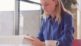 Young, beautiful woman using tablet and drinking tea in the cafe stock video