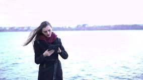 Young beautiful woman using tablet near lake stock video