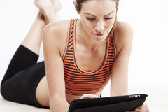 Young beautiful woman using a tablet after workout Royalty Free Stock Photos