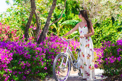 Young beautiful woman on vacation biking at lush Royalty Free Stock Photo