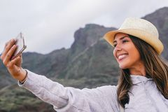 Young beautiful woman in vacation taking a selfie with her mobile smartphone camera with mountain in the background stock photo