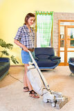 Young beautiful woman with vacuum cleaner at home. royalty free stock image