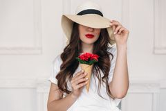 Young beautiful woman vegan portrait, wearing a straw hat with large fields and covering her eyes, lips red. The girl royalty free stock photos