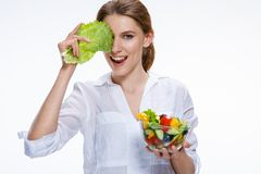 Young beautiful woman with vegetable salad bowl in one hand and cabbage leaf in other hand  on white background Royalty Free Stock Image
