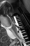 Young beautiful woman in a vest playing the piano. Black-and-white, from overhead angle Stock Photos
