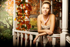 Young beautiful woman in vintage dress on autumn porch. Beauty g Royalty Free Stock Photography