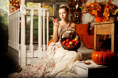 Young beautiful woman in vintage dress on autumn porch. Beauty g Stock Photography