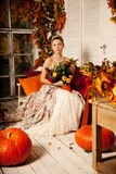 Young beautiful woman in vintage dress on autumn porch. Beauty g Stock Images