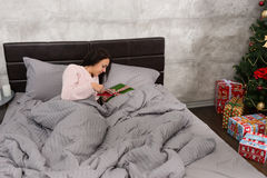 Young beautiful woman wake up and looking at her christmas prese Royalty Free Stock Photography