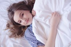 Young beautiful woman waking up fully rested. Beautiful young woman waking up fully rested. Rest, sleeping, comfort and people concept - teen girl lying in the Stock Images