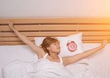 Young beautiful, woman waking up fully rested in the morning. Background Royalty Free Stock Photos
