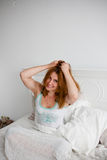 Young beautiful woman waking up fully rested. Young beautiful red woman waking up with disheveled red hair Royalty Free Stock Photos