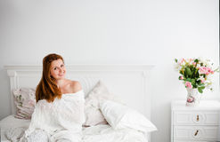 Young beautiful woman waking up fully rested. Young beautiful red woman waking up fully rested in light interior Royalty Free Stock Photos