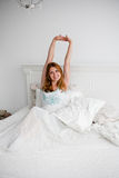 Young beautiful woman waking up fully rested. Young beautiful red woman stretching in white bed Royalty Free Stock Photo