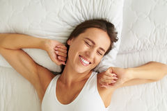 Young beautiful woman waking up in her bed fully relaxed. Young beautiful woman waking up in her bed fully rested. Woman stretching in bed after awakening Royalty Free Stock Image
