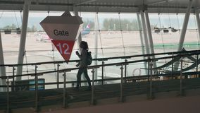 Airport Gate 12 View. Young and beautiful woman is walking airport hall with luggage near gate 12 stock video footage