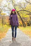 Young beautiful woman walking along autumn city park. Young stylish smiling woman dressed in oversized knitted sweater, skinny jeans, peaked cap and heels Royalty Free Stock Image