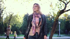 Portrait of an attractive woman against the setting sun in autumn Park. slow motion. Young beautiful woman walking on autumn park. the girl turns on the camera stock video