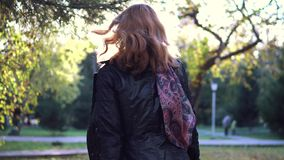 Portrait of young woman in autumn Park. the girl in the scarf and coat playfully turns and looks at the camera. slow. Young beautiful woman walking on autumn stock video footage
