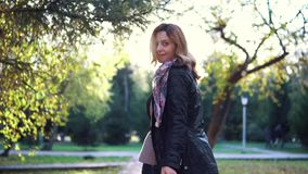 Young beautiful woman walking on autumn park. the girl turns on the camera. back view. slow motion. Young beautiful woman walking on autumn park. the girl turns stock video