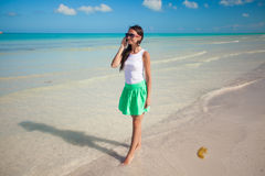 Young beautiful woman walking on the beach talking Stock Photography