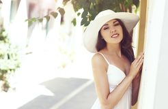 Beautiful lady walking down the street in a white dress. Stock Photography