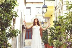 Beautiful lady walking down the street in a white dress. Stock Image