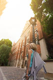 Young beautiful woman walking down the street along an old brick building against the background of sunlight Royalty Free Stock Images