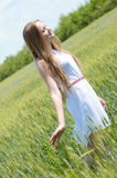 Young beautiful woman walking in green wheat field on summer day Royalty Free Stock Photo