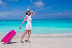 Young beautiful woman walking with her bag on tropical beach Stock Photo
