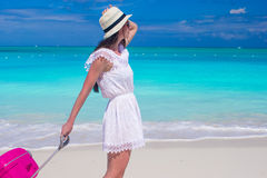 Young beautiful woman walking with her luggage on tropical beach Stock Images