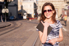 Young beautiful woman walking in the morning town with a book an Stock Photo