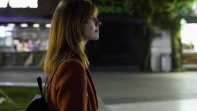 Young beautiful woman walking at night in the city. Red-haired woman on the stree. Slow Motion stock video footage
