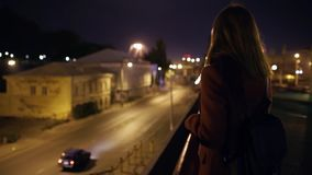 Young beautiful woman walking at night in the city. Red-haired woman on the stree. Slow Motion stock video